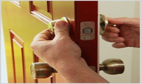 cerrajero instalando cerradura en puerta de madera